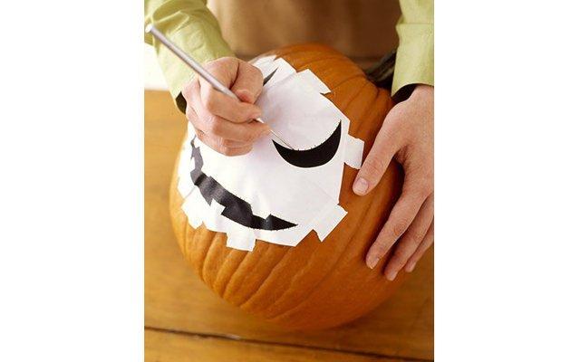 Как вырезать тыкву на Хэллоуин?: [b]Шаг 3:[/b] Используйте готовый шаблон, или  нарисуйте его сами маркером на бумаге. Приклейте шаблон скотчем к тыкве и перенесите