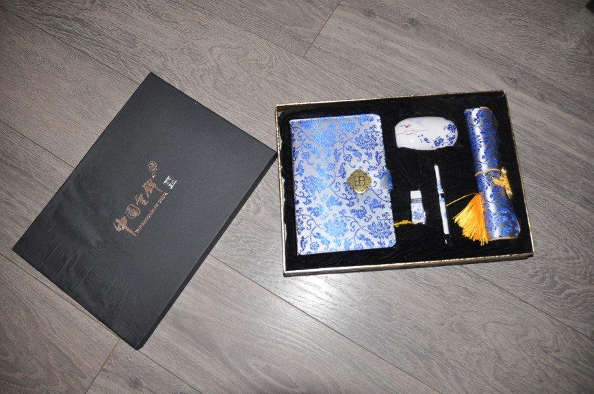 Флешка беспроводная мышка блокнот для записей коврик в подарочной коробке. Привезен в подарок из Китая, но т.к. в чемодане повреждена была крышка от коробки было неудобно дарить. Подарок дорогой, покупался целенаправленно, но увы. Ручка и флешка из фарфора, коврик и обложка для блокнота из расшитого китайского плотного шелка. Флешка 8 ГБ. Стоил этот подарок около 100 долларов. 2500р