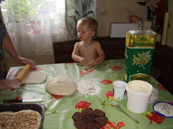 помогает бабушке делать пирог
