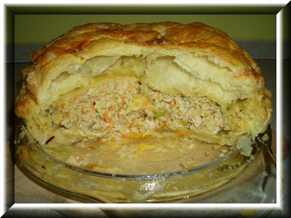 Пирог из слоеного теста с фаршем Раскатать упаковку слоеного теста на два пласта, уложить один пласт в смазанную форму или на противень. Пропустить через мясорубку 0,5 кг. свинины, морковь, лук, 2 зубка чеснока, добавить 50 г сливочного масла размягчённого, полстакана неварёного риса и соль-перец. Начинку хорошо перемешать и уложить на тесто, накрыть второй частью теста, защипать края, наколоть верх и смазать яйцом. Выпекать при 200 С до готовности. Я пекла в микроволновке на режиме микро 600В + конвекция 220С - 10 минут, потом 10 минут на микро 600В + конвекция 180С.