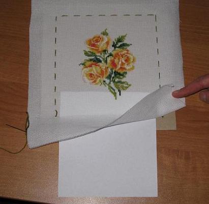 Доходя до углов, аккуратно убираем наши намёточки, и пришиваем. Когда остаётся прошить одну сторону, вставляем между канвой и картоном лист белой бумаги.