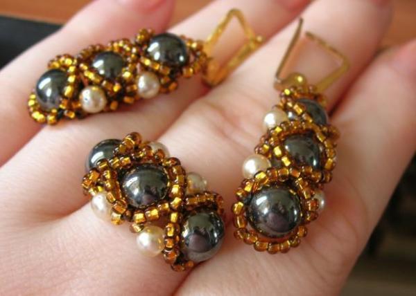 Навеяно кольцом ВоробьяВаси ( http://www.eva.ru/albumpage/63200/6.htm ). Кольцо - бусины из полированного гематита, искусственный жемчуг, золотой бисер. Серьги повторяют внешнюю часть кольца.