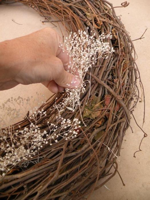 Как сделать рождественский венок?: Вплетите в лицевую часть веточки сухой травы (или искусственные веточки).