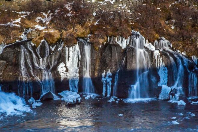 Водопад Hraunfossar, необычен тем, что вода вытекает из подземной речки в лавовом поле, образуя водопады высото 5-6 метров на протяжении 900 метров