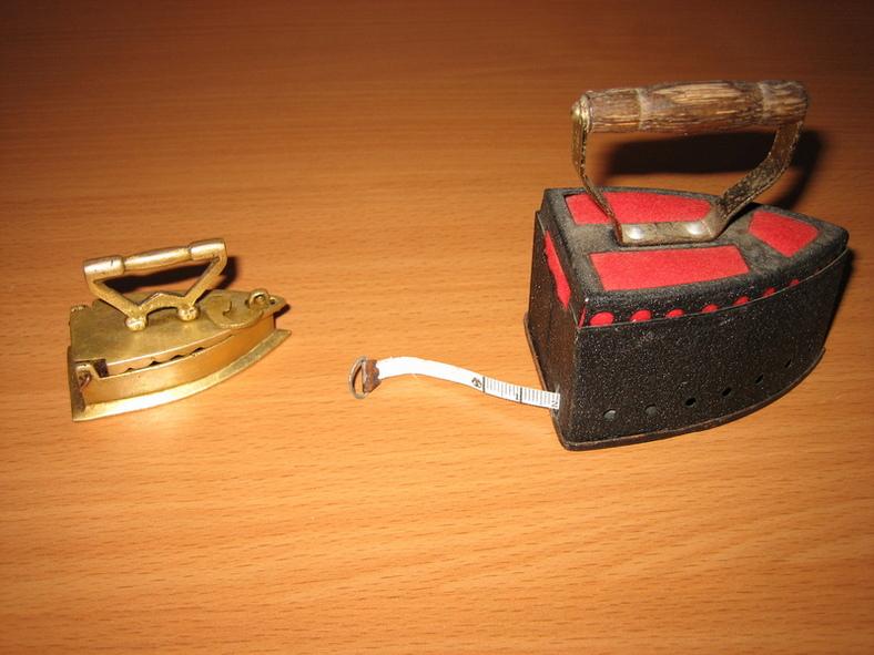 66. Маленький латунный сувенирный утюжок, его размер 6,3 см на 3,2 см;                    67. Черный утюг-игольница с красными вставками-подушечками для иголок и сантиметром, скрытым за задней стенкой утюга.