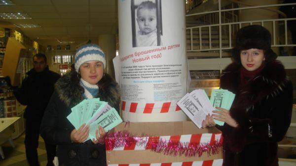 Девочки-волонтеры из ЗабИИЖТА в магазине Амелия. И наш основной плакат над ними