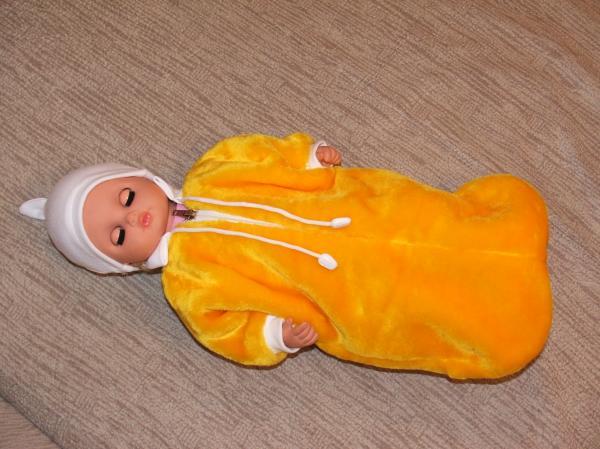 Наша лялька в меховом конверте и трикотажной шапочке.